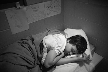 Photo of boy asleep on prison bed. Credit Steve Liss